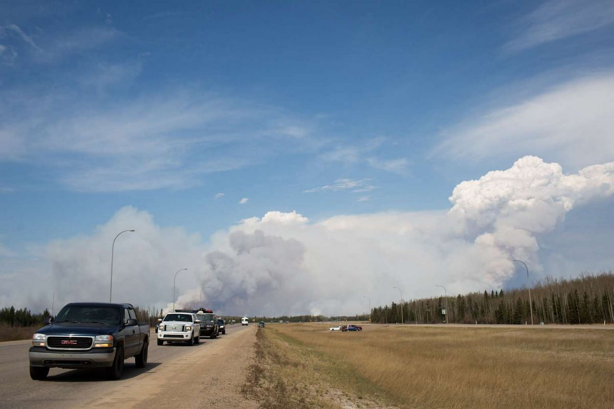 Vehicles drive away from Fort McMurray as winds pick up and smoke begins to darken just south of Fort McMurray, Alberta, Canada.