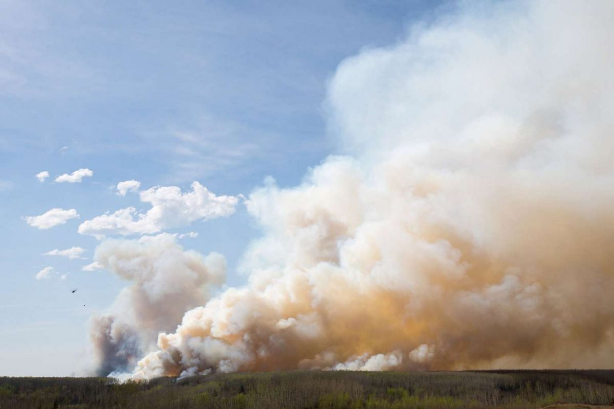 A helicopter flies past thick smoke while battling a major forest fire outside of Fort McMurray.