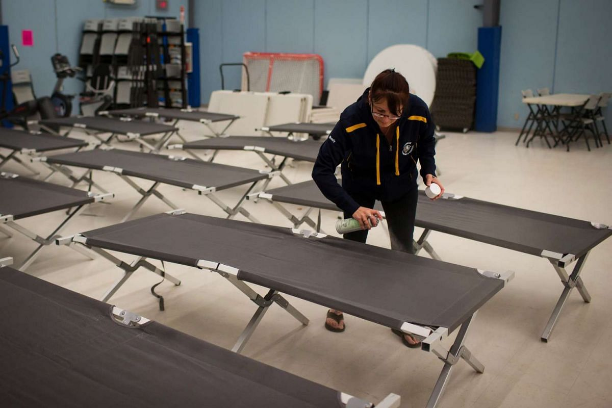 Wendy Tremblay, resident of Conklin, Alta., prepares cots for residents of Fort McMurray.
