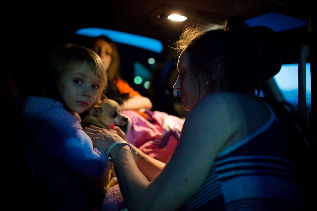 Fort McMurray resident Crystal Maltais buckles in her daughter, Mckennah Stapley, as they prepare to leave Conklin, Alberta.