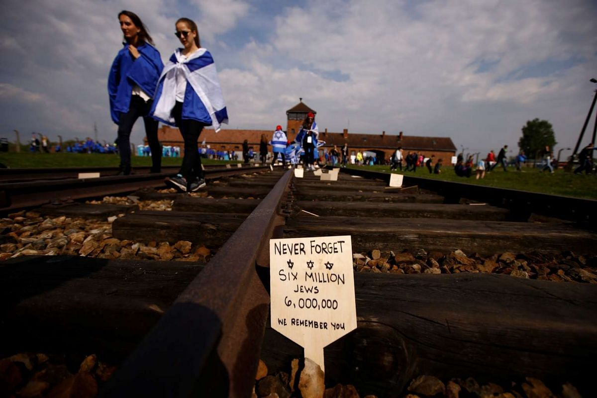 """A card is placed between railway tracks as people march in the former Nazi death camp of Auschwitz-Birkenau (Auschwitz II) as thousands of people, mostly youth from all over the world gathered for the annual """"March of the Living"""" to commemorate the H"""