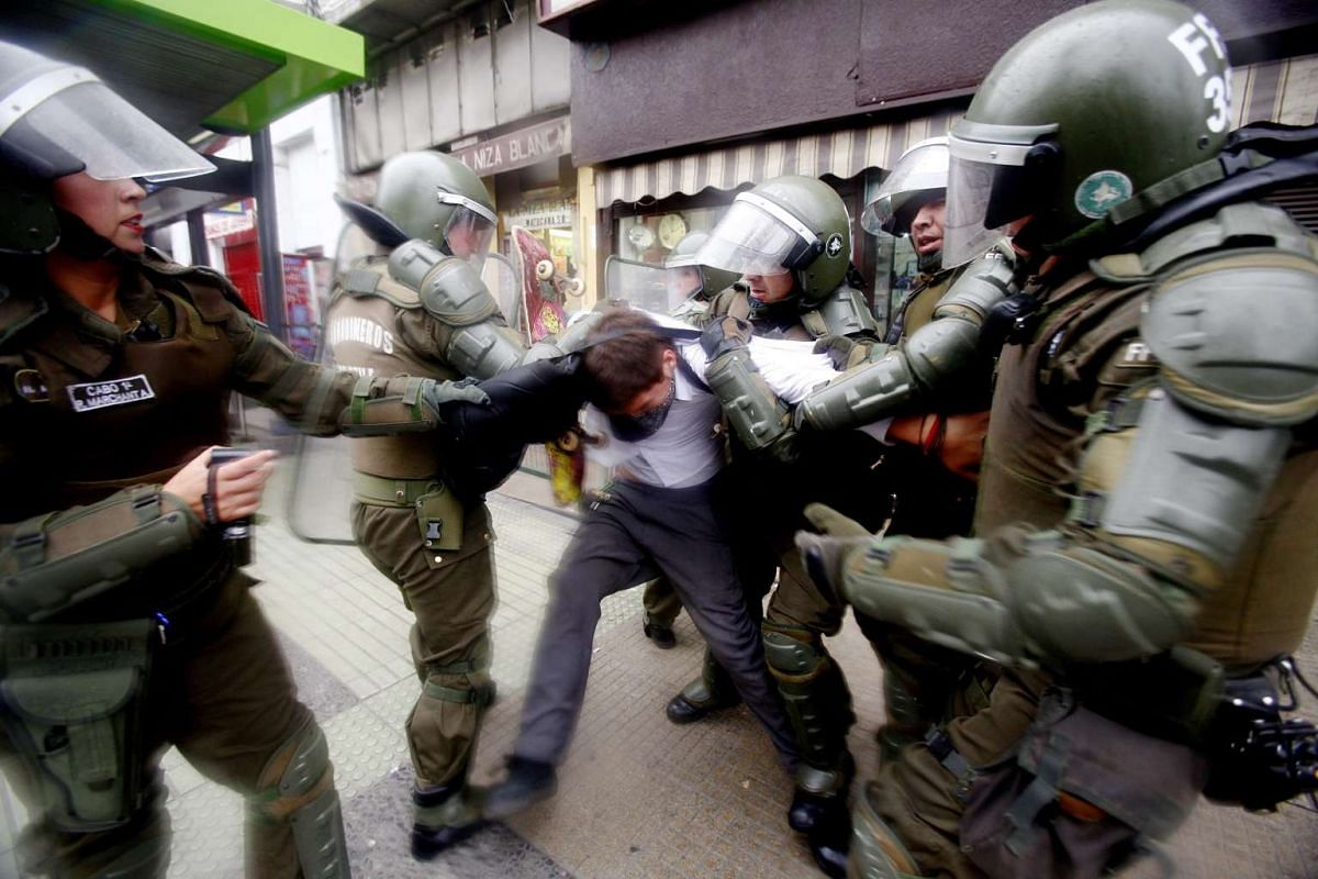 A demonstrator is detained by anti-riot police during a student demonstration to call for the expansion of free education programs and the reinstitution of student benefits, in Santiago, Chile, May 5, 2016. PHOTO: EPA