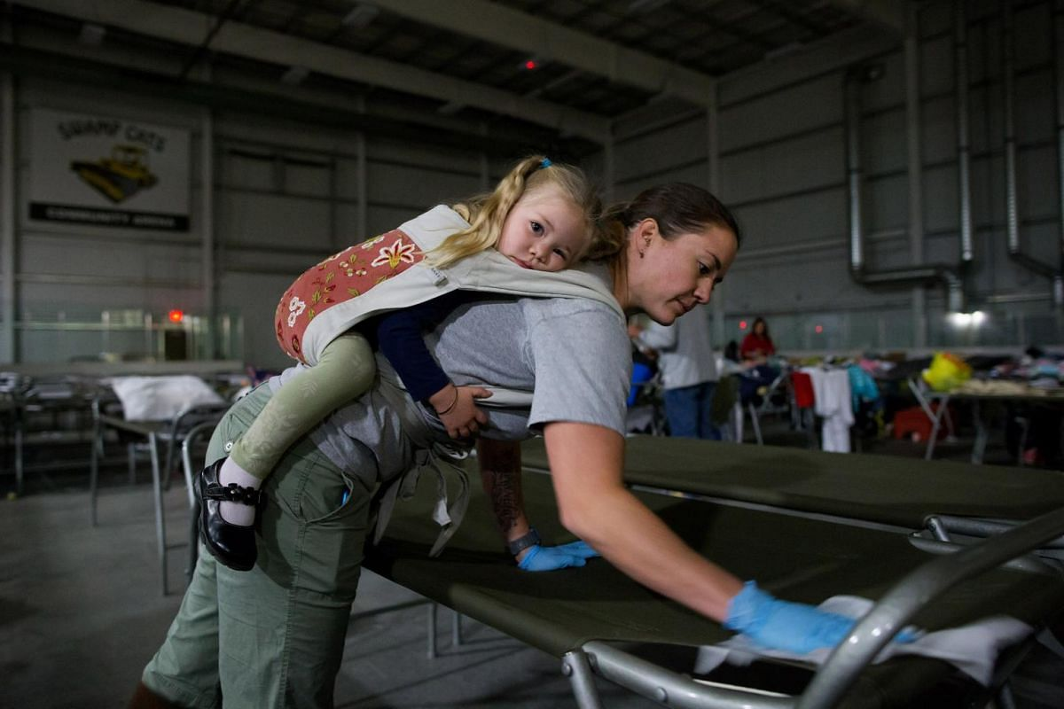 A volunteer carries her daughter while cleaning cots for wildfire evacuees at a hockey rink in Lac La Biche, Alberta, Canada, on May 5, 2016.