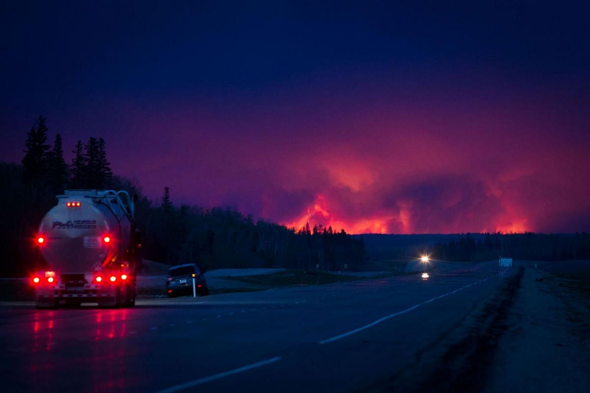 A truck drives on a highway as a wildfire burns south of Fort McMurray, Alberta, Canada, on May 4, 2016.