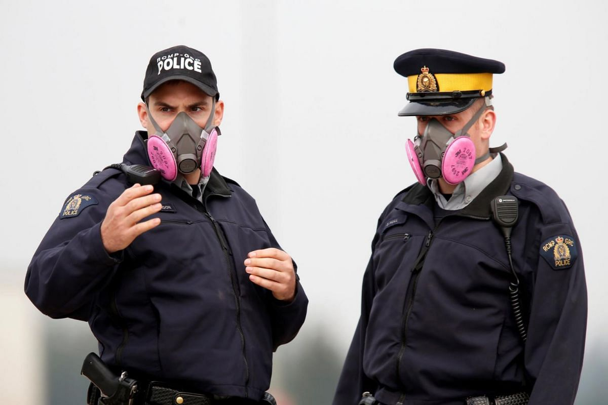 Royal Canadian Mounted Police officers wear masks to protect themselves from smoke while directing traffic in Alberta, Canada, on May 5, 2016.