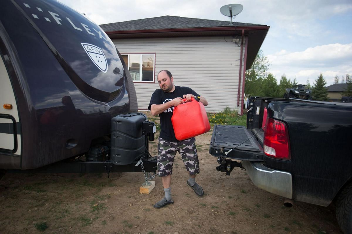 Fort McMurray wildfire evacuee A.J. Rosenthal carries a can of gas for his generator in Plamondon, Alberta, Canada, on May 5, 2016.