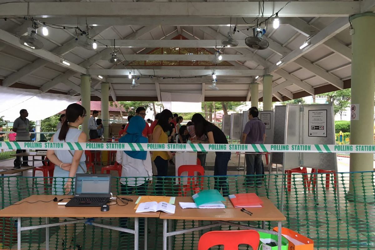 Boxes being inspected by polling agents at the polling station at Block 105A, Bukit Batok Central.