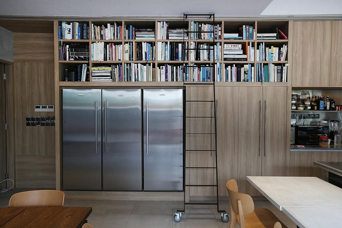 Wood panelling and cookbooks placed on shelves above three fridges.