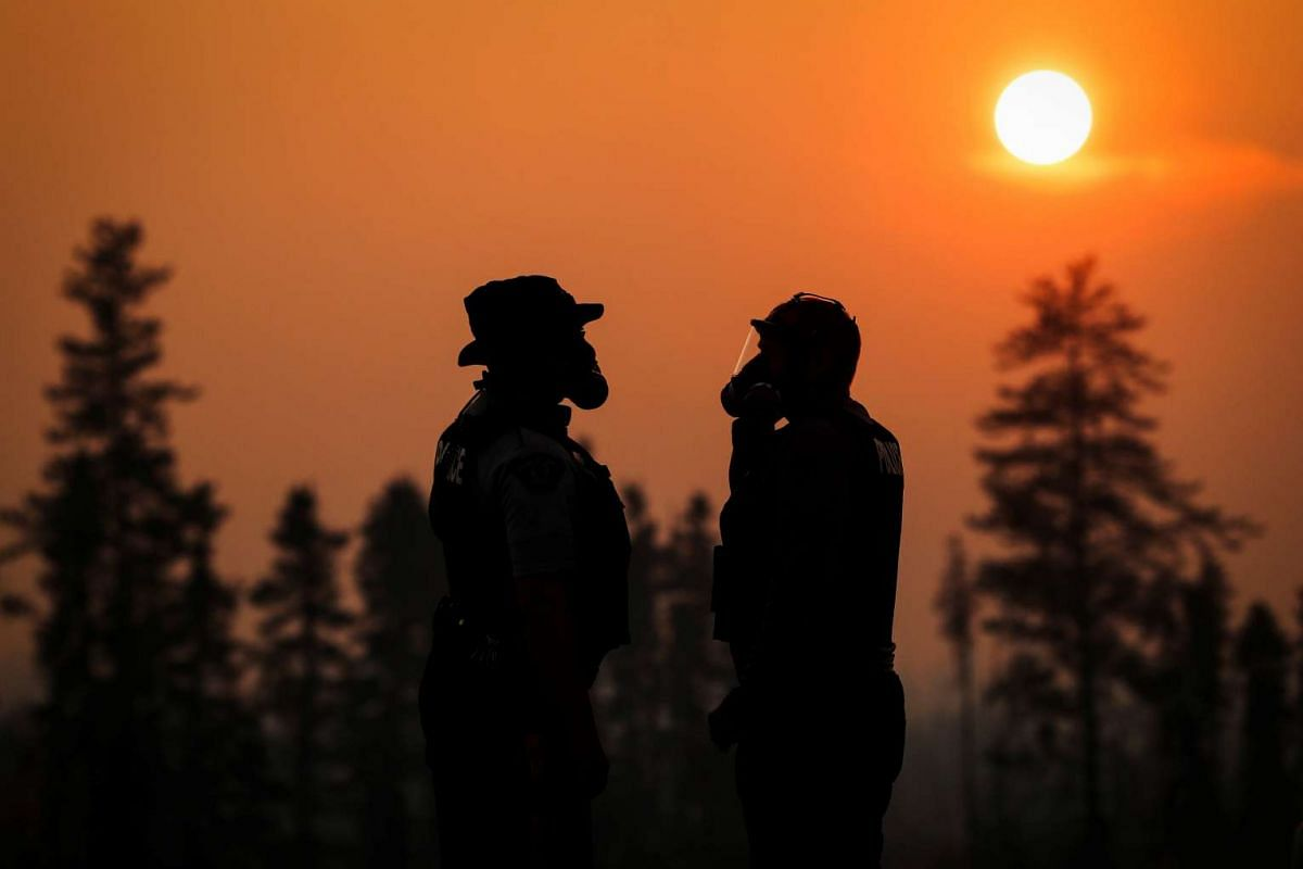 Two police officers wearing gas masks in the smoke from the wildfires near Fort McMurray on May 6.
