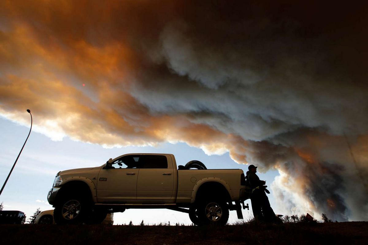People waiting at a roadblock as smoke rises from wildfires near Fort McMurray on May 6.