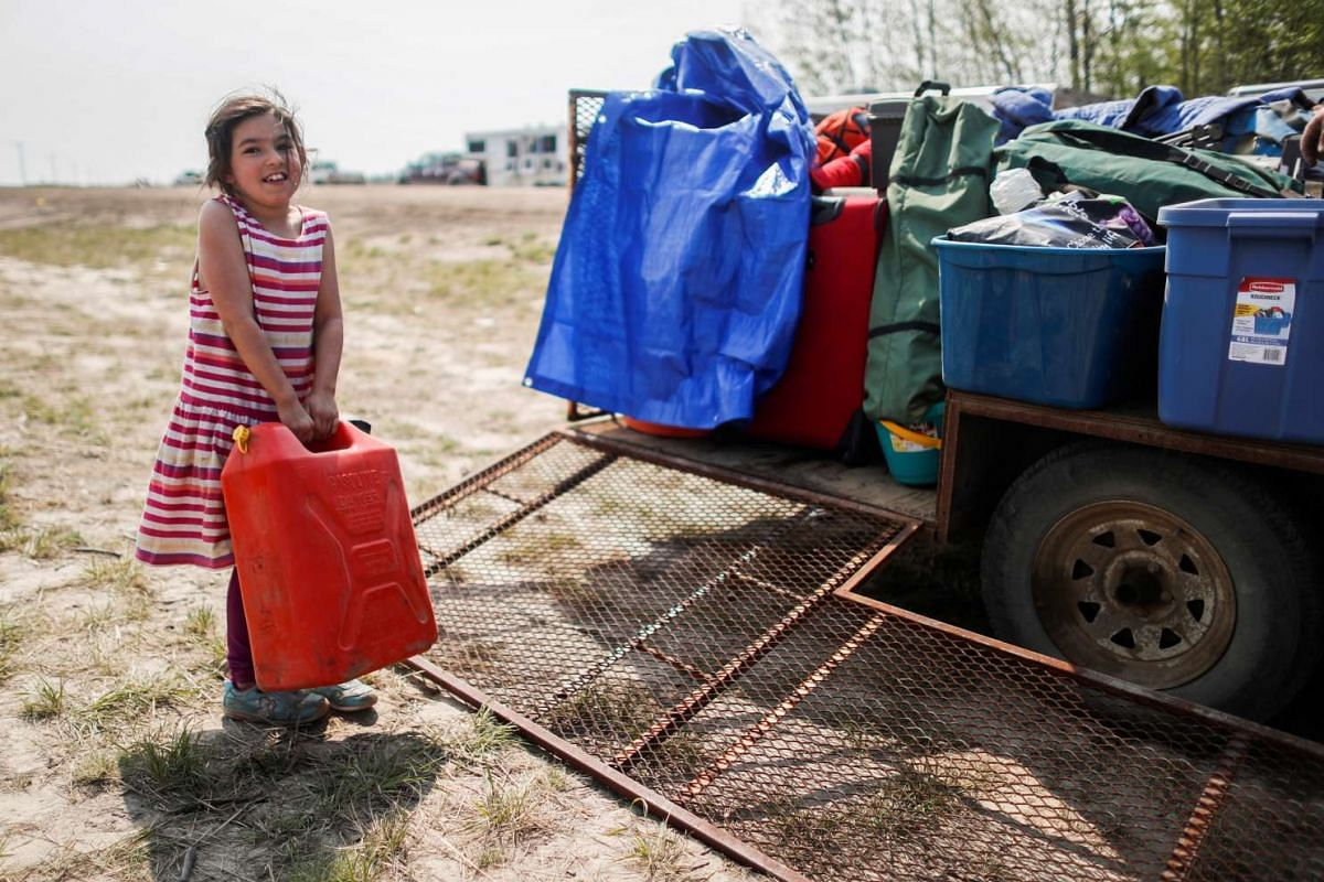 Clieo Wendel holds a petrol can as she helps her family pack a trailer in Wandering River, Canada, on May 6.