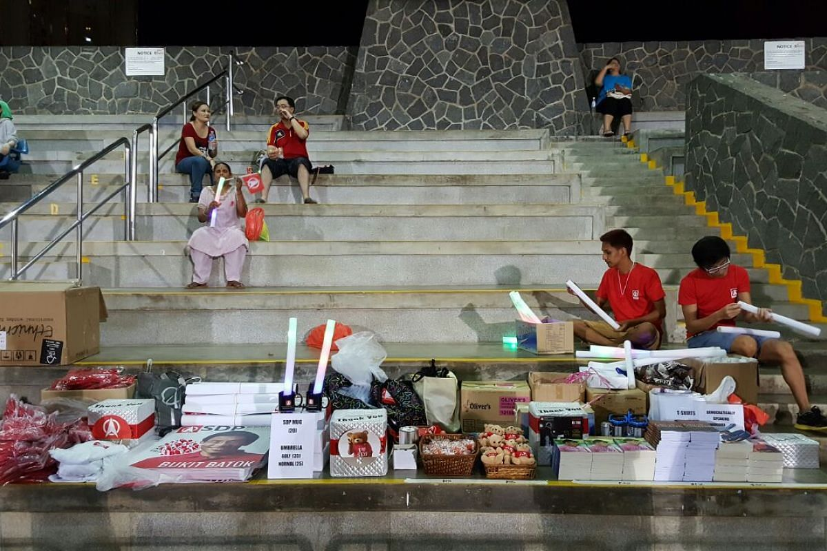 Singapore Democratic Party merchandise on sale next to a supporters' area on Saturday evening.