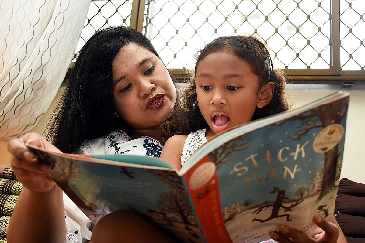 Adjunct teacher Suriati Abdolah reading with her daughter, Safa Zara Atiya, six.