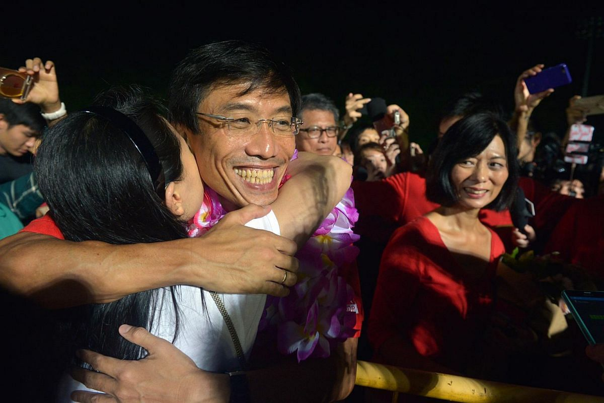 SDP's Chee Soon Juan being hugged by a supporter at Bukit Gombak stadium.