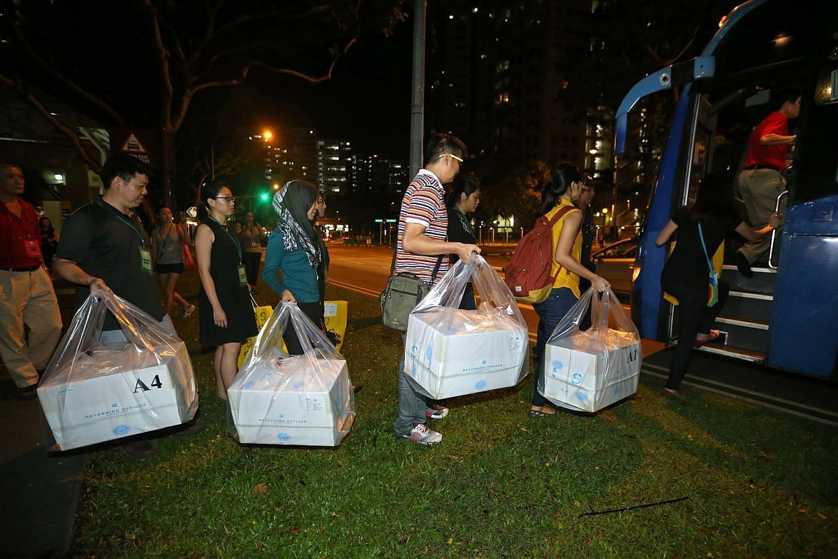 Polling agents from polling station Blk 105A loading ballot boxes onto an awaiting bus at Bukit Batok Central after the polls closed at 8pm.