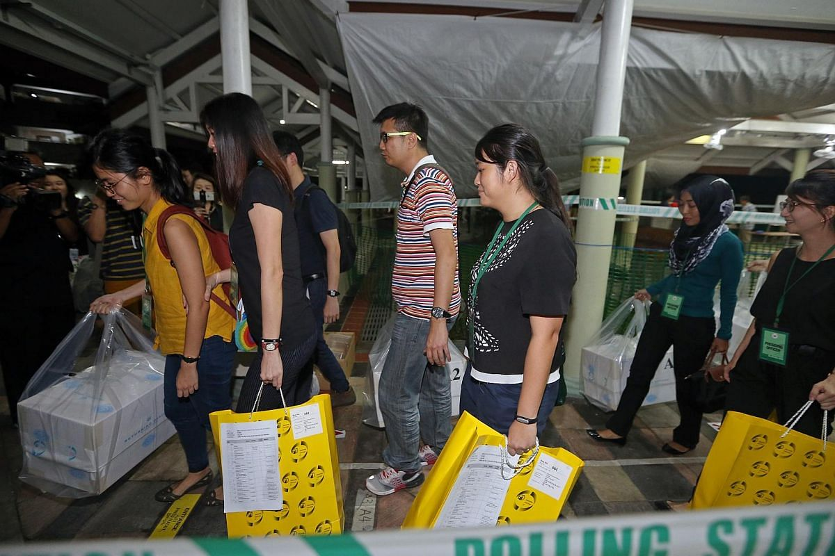 Polling agents from polling station Blk 105A bringing ballot boxes to an awaiting bus at Bukit Batok Central after polls closed at 8pm.
