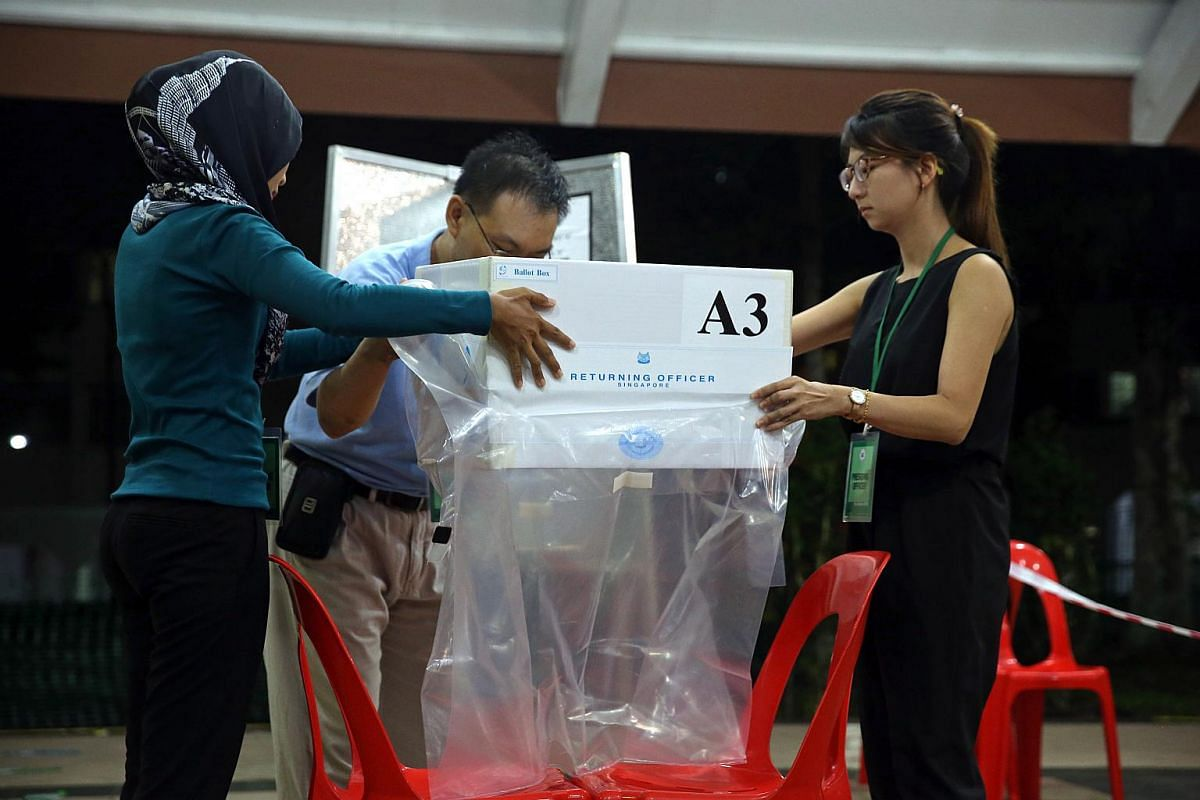 Polling agents inspect and seal poll boxes at polling station Blk 105A Bukit Batok Central after polls closed at 8pm.