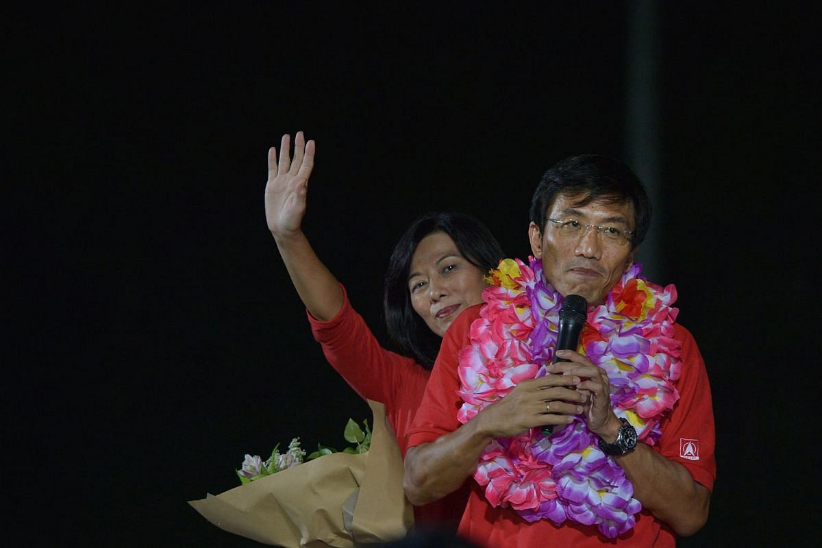 Chee Soon Juan and his wife, Huang Chih-Mei, stand on a table at Bukit Gombak stadium, thanking supporters who waited for the results which was announced after 11pm.