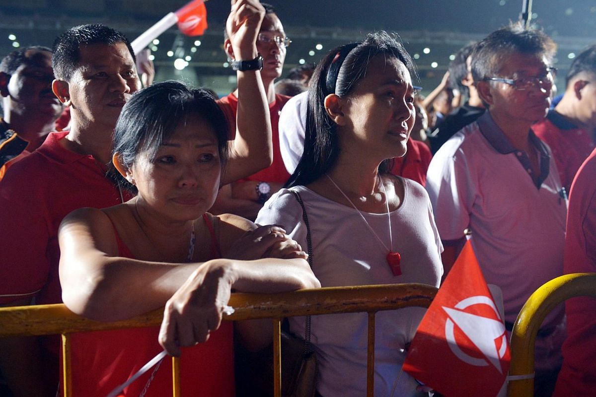 Disappointed supporters of Chee Soon Juan listen to his address after his loss at the Bukit Batok by-election at the Bukit Gombak Stadium.