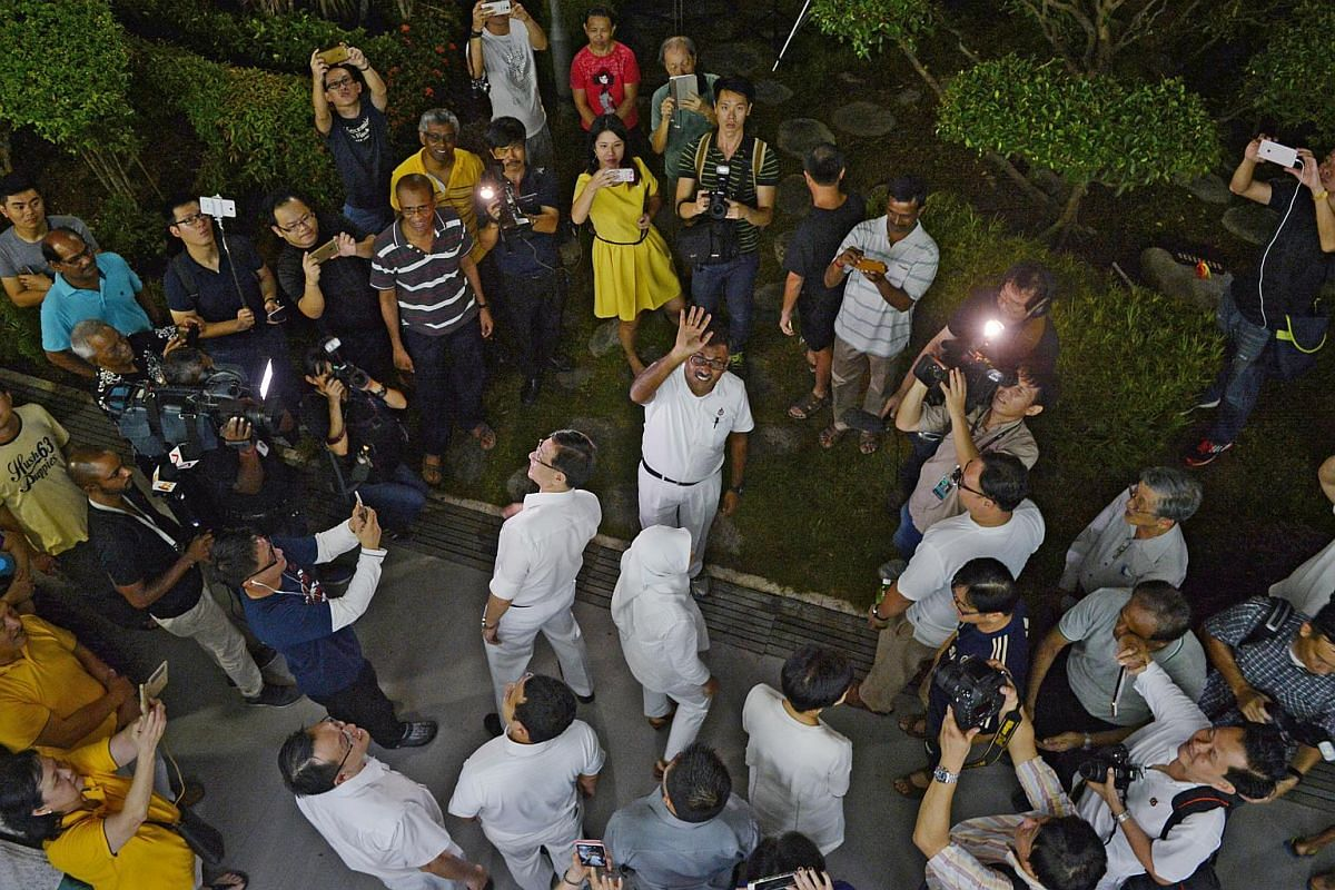 PAP's Murali Pillai waves to supporters at the PAP branch office before the results were announced.
