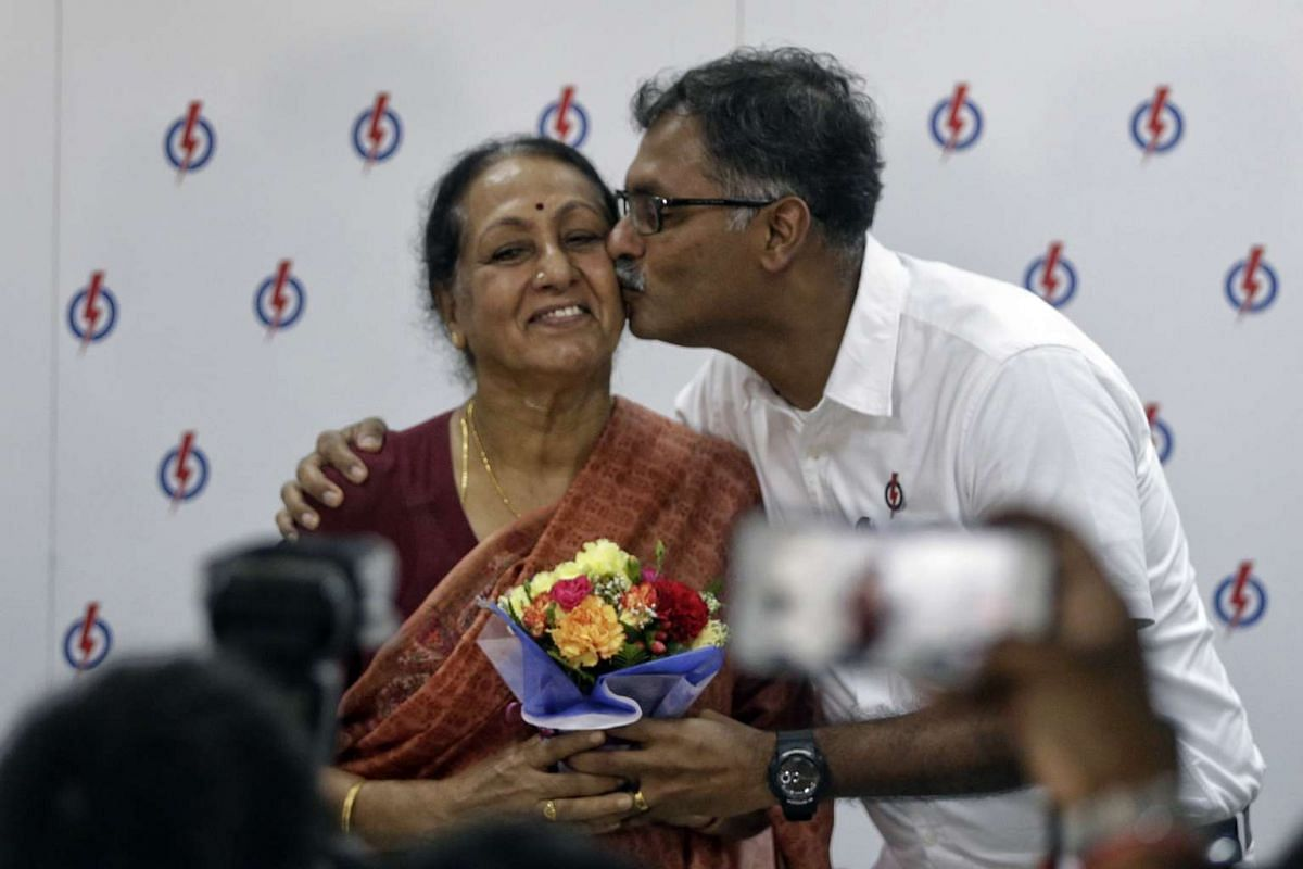 Winning candidate Murali Pillai presenting flowers to and kissing his mother after his victory.