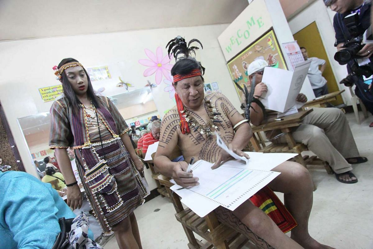 Tribal leader Nicolas Cawed (centre), assisted by his daughter Mia Nicole (left), casts his vote at a polling station in Baguio City, Manila, on May 9, 2016.