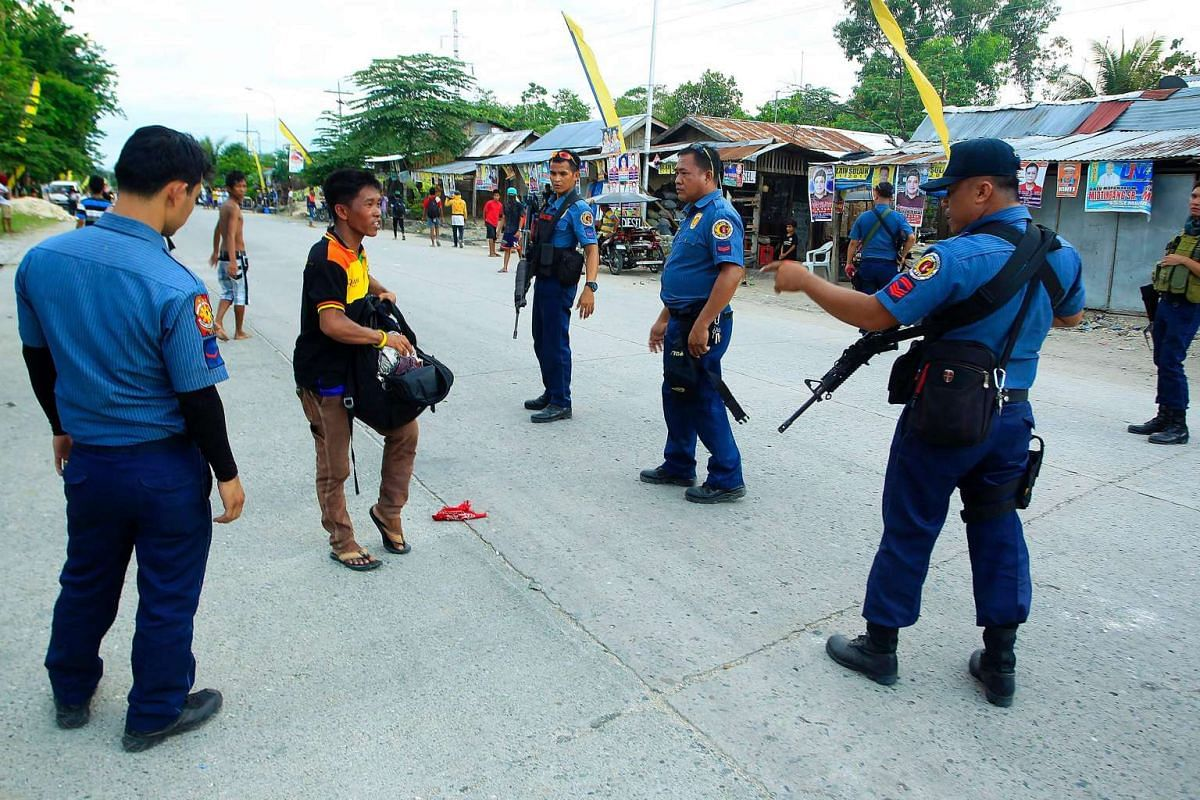 Philippine policemen checking a man at a checkpoint along a highway in Datu Unsay town, Maguindanao.