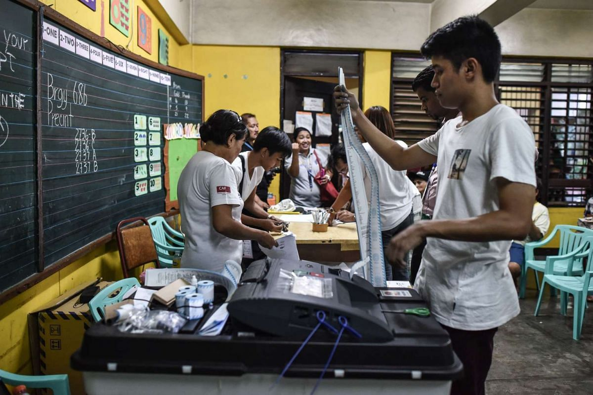 A polling officer (right) holds printed documents from a vote counting machine after polls closed in the presidential election in Manila, on May 9, 2016.