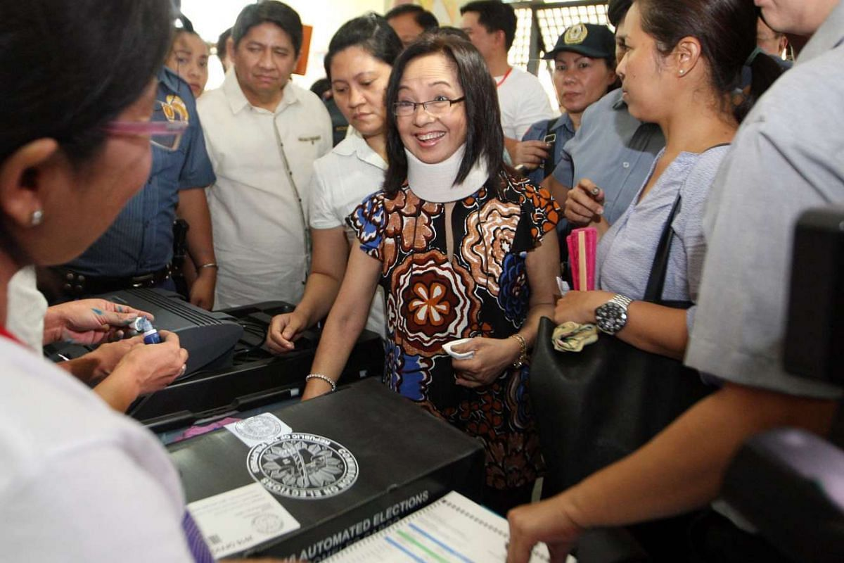 Former Philippine president Gloria Macapagal Arroyo (centre) wearing a neck brace casts her vote in the town of Lubao, Philippines, on May 9, 2016.