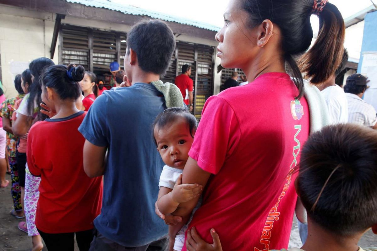 A woman carries her child as she queues with other residents to vote during the national elections in Davao city, in southern Philippines, on May 9, 2016.