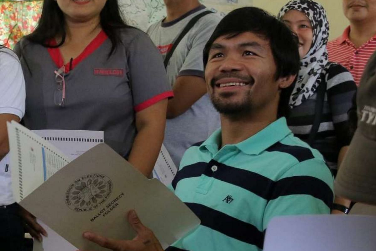 Filipino boxing champion Manny Pacquiao throws his receipt after casting his vote in Kiamba, Sarangani province, Philippines, on May 9, 2016.