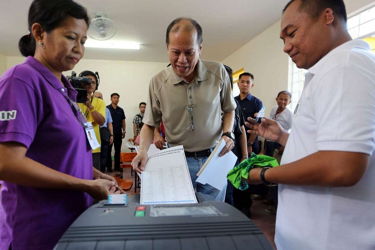 Philippine President Benigno Aquino III (centre) casts his vote at a polling precinct in Tarlac, Philippines, on May 9, 2016.