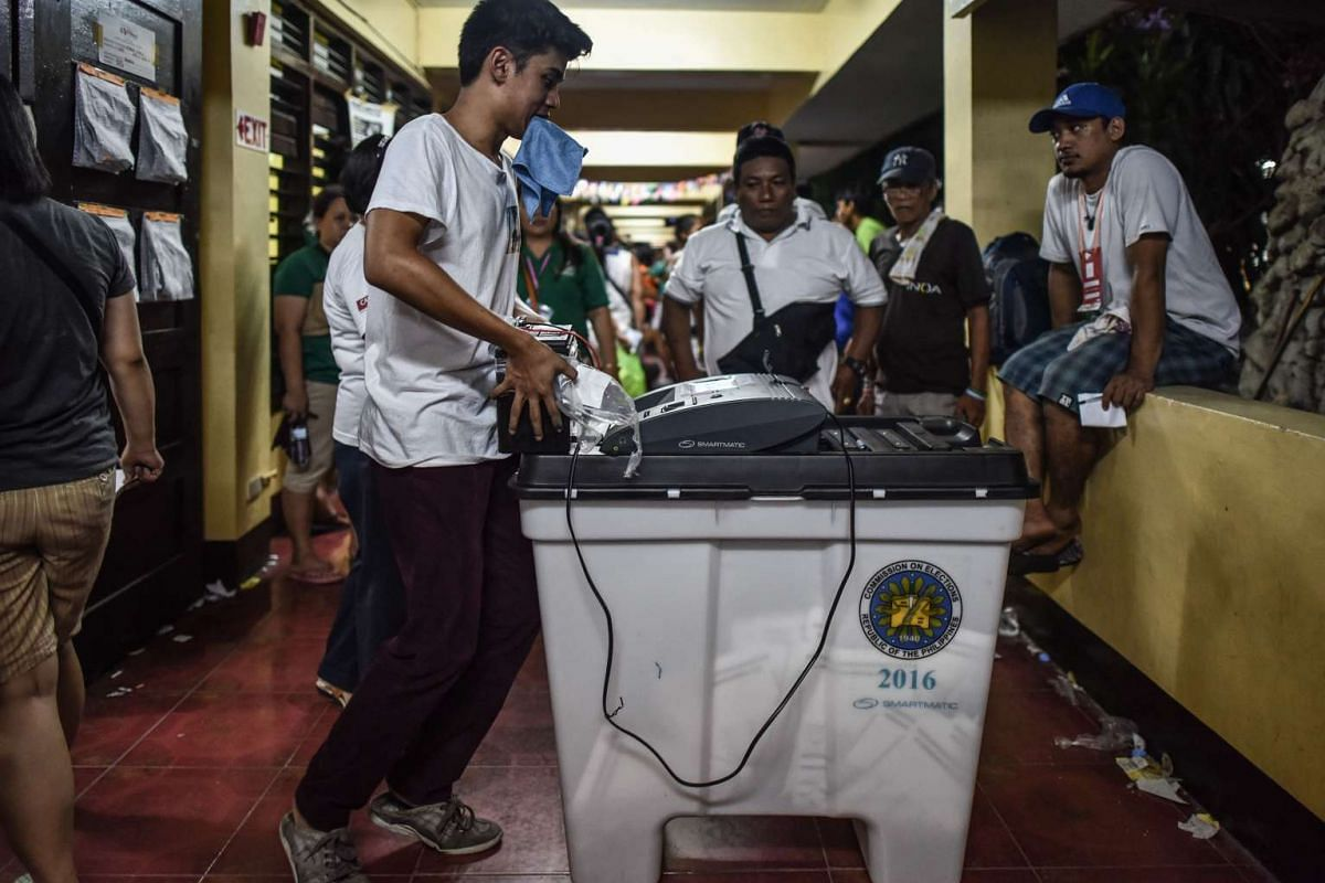 A polling officer pushes a vote counting machine after polls closed in the presidential election in Manila, on May 9, 2016.