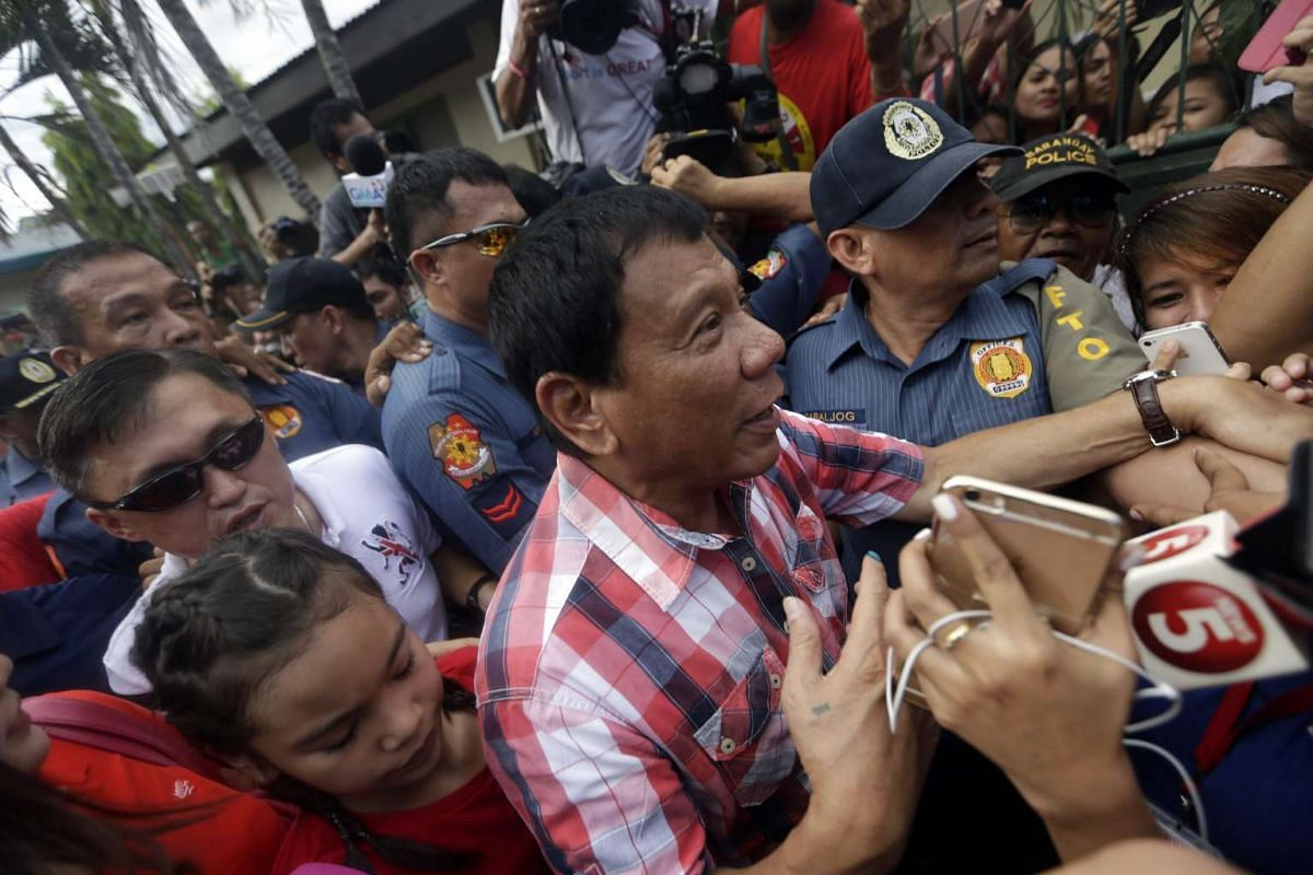Philippine presidential candidate Rodrigo Duterte is surrounded by supporters after casting his vote in Davao City, on May 9, 2016.