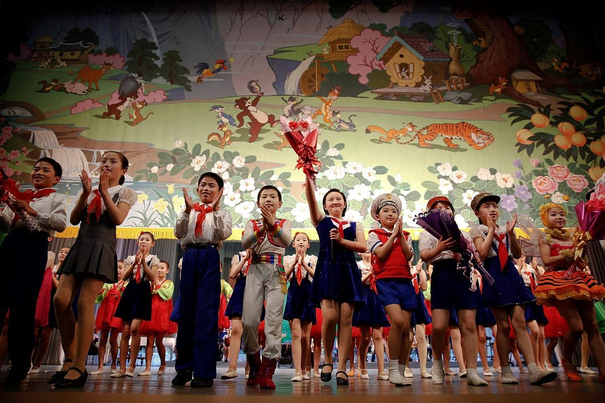 Children wave to spectators as the curtain is brought down at the end of a performance at the Mangyongdae Children's Palace in Pyongyang.