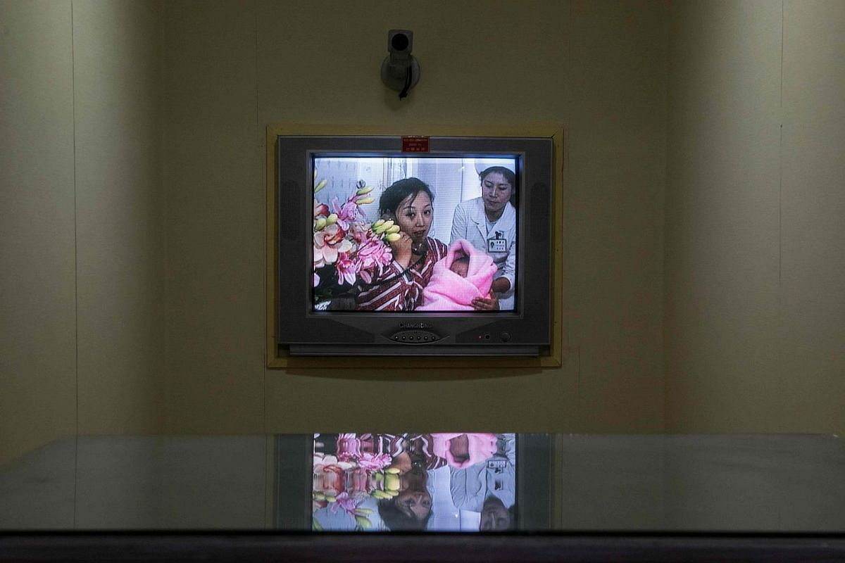 A new mother holds her baby as she talks via telephone on a screen to journalists at the Pyongyang Maternity Hospital during a government-organised media tour in Pyongyang.