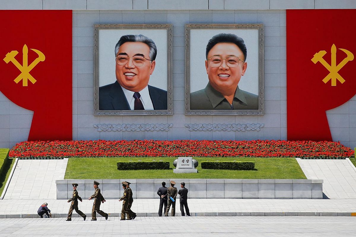People stand in front of pictures of former North Korean leaders Kim Il Sung (left) and Kim Jong Il at the main Kim Il Sung square in central Pyongyang.