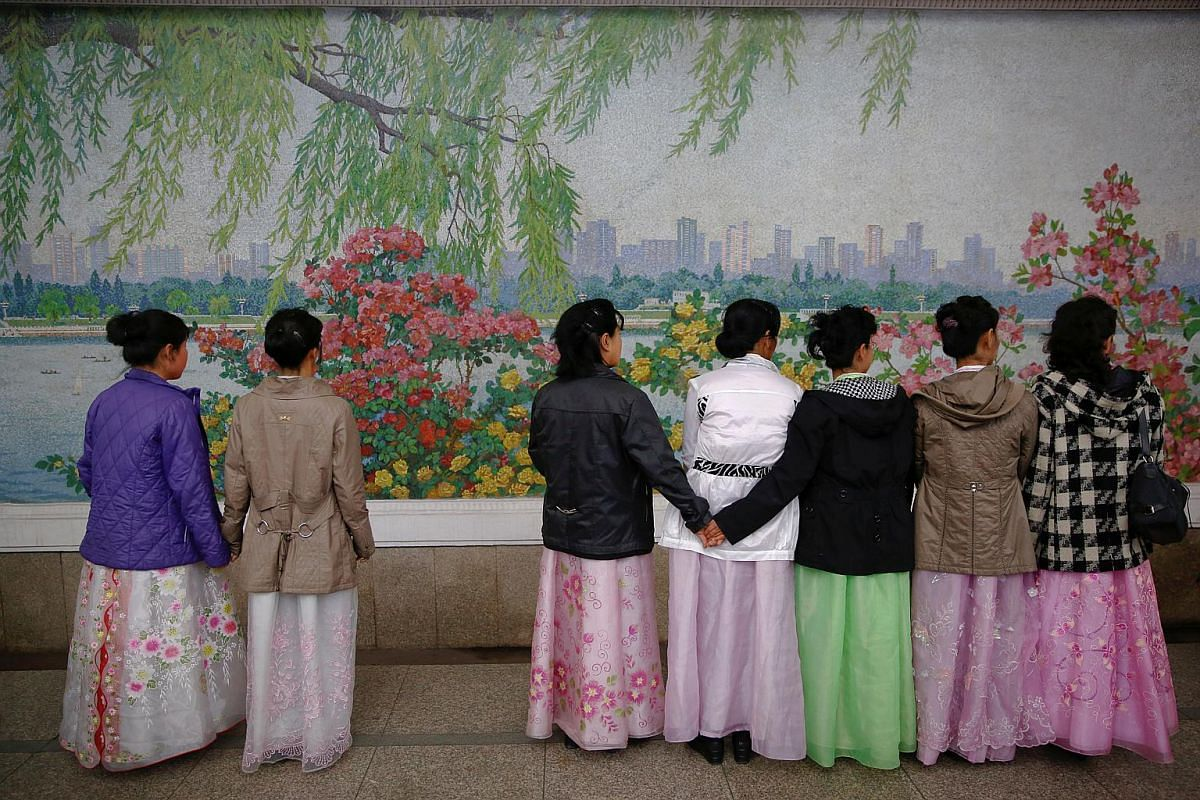 Women wearing traditional clothes wait for the train inside a subway station in central Pyongyang.