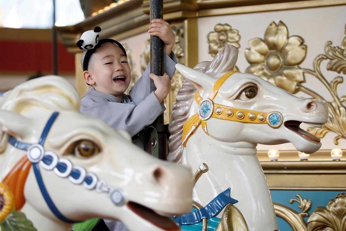 A boy, who is experiencing the lives of Buddhist monks by staying in a temple for two weeks as novice monk, enjoys a ride at the Everland amusement park in Yongin, South Korea, on May 9, 2016.