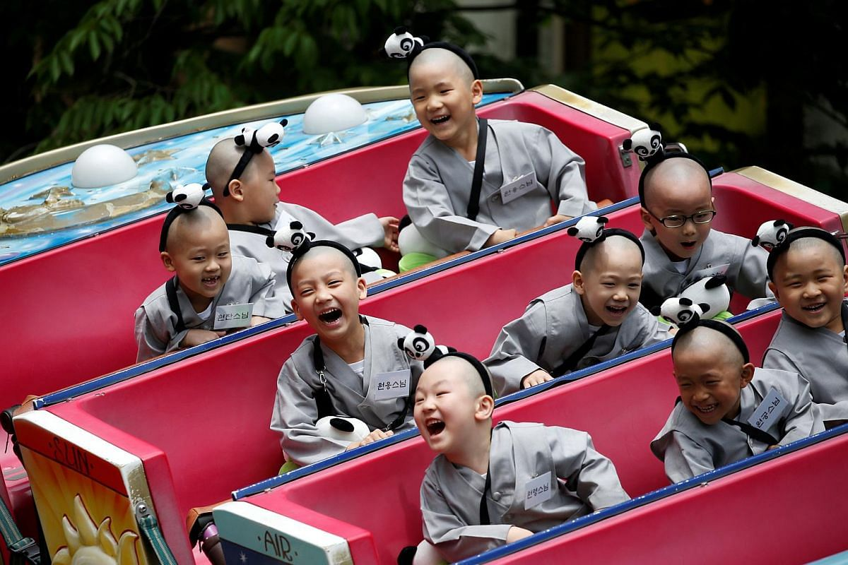 Boys, who are experiencing the lives of Buddhist monks by staying in a temple for two weeks as novice monks, enjoy a ride at the Everland amusement park in Yongin, South Korea, on May 9, 2016.