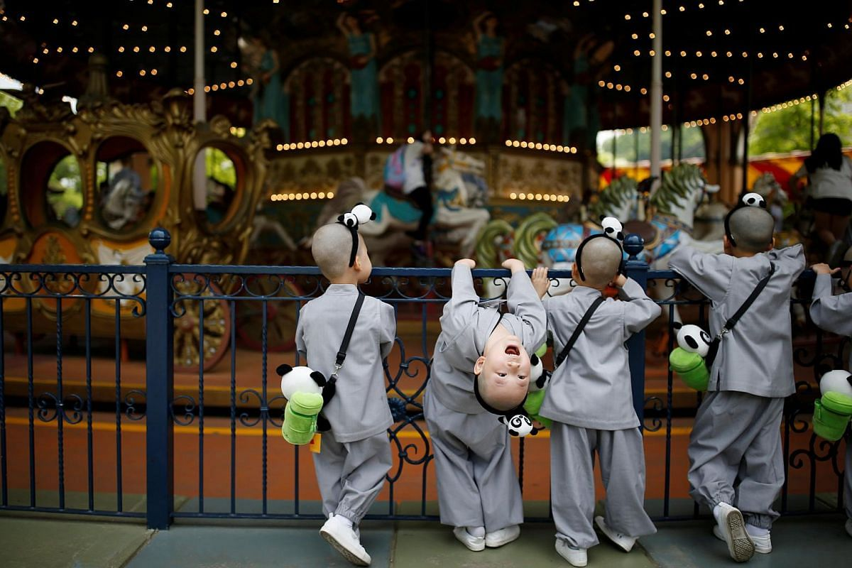 Boys, who are experiencing the lives of Buddhist monks by staying in a temple for two weeks as novice monks, look at a carousel at the Everland amusement park in Yongin, South Korea, on May 9, 2016.