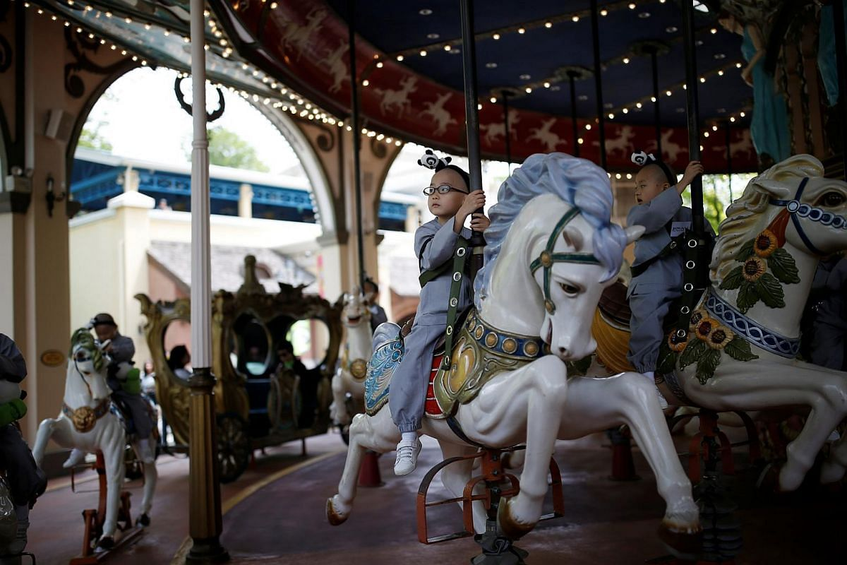 Boys, who are experiencing the lives of Buddhist monks by staying in a temple for two weeks as a novice monk, ride on a carousel at the Everland amusement park in Yongin, South Korea, on May 9, 2016.