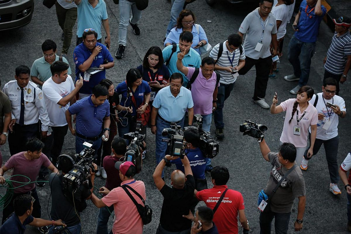 Filipino presidential candidate, Vice president Jejomar Binay gets surrounded by the media as he walks from his home to a public school turned into a polling precinct in Manila.