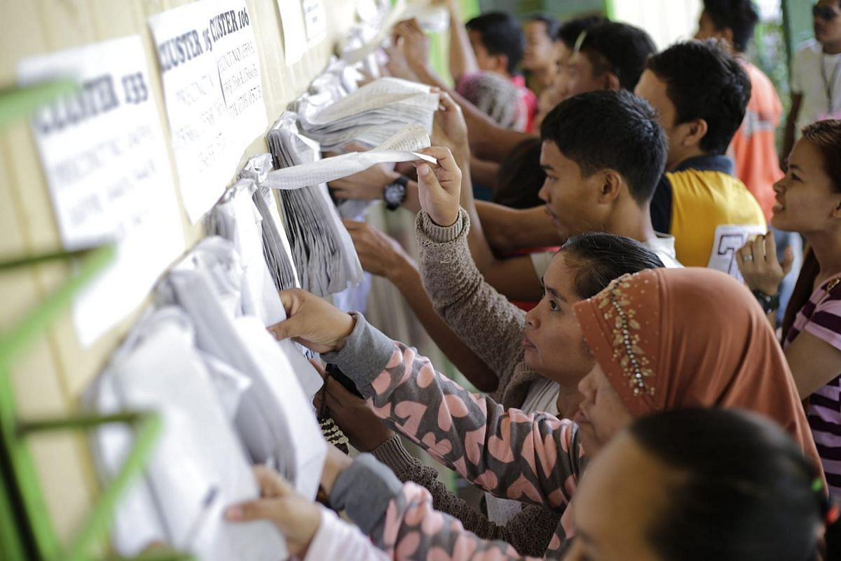 Filipino voters look for their names as they prepare to cast their votes during the National Election Day in Davao city, Philippines.