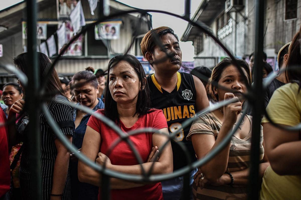 Filipino voters queue outside the gate of a polling station before the presidential and vice presidential elections at a polling centre in Manila on May 9, 2016.