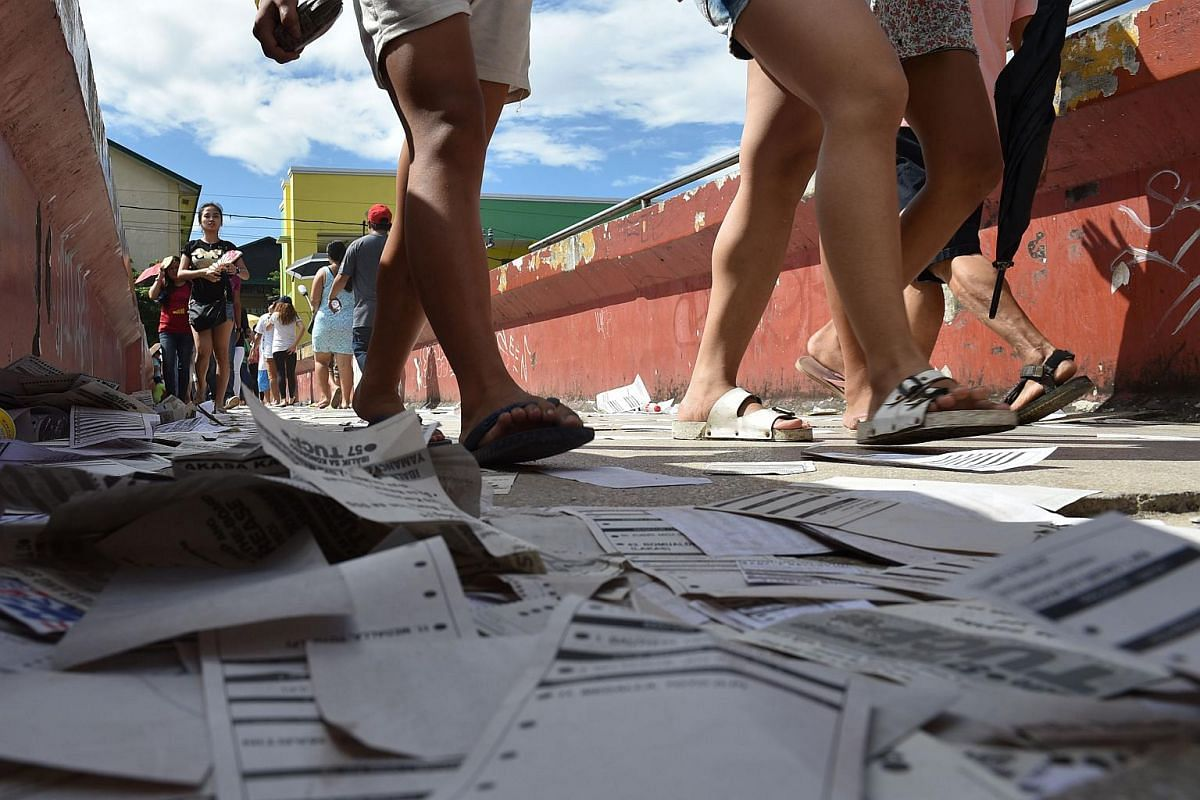 People walk over election posters and sample ballots for the presidential election scattered on a footbridge near a polling station in the Quezon City district, Manila.