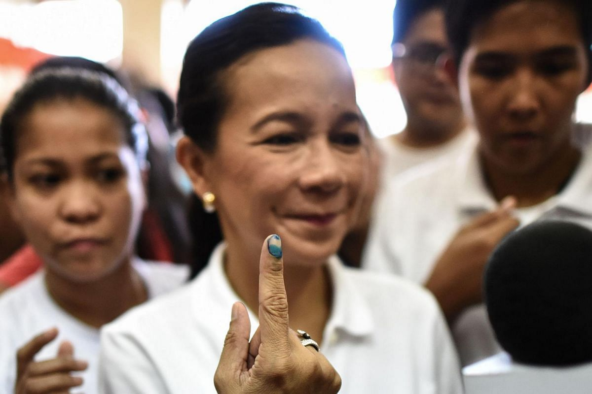 Philippine presidential candidate Senator Grace Poe (centre) shows her finger covered with indelible ink after casting her vote, on May 9, 2016.