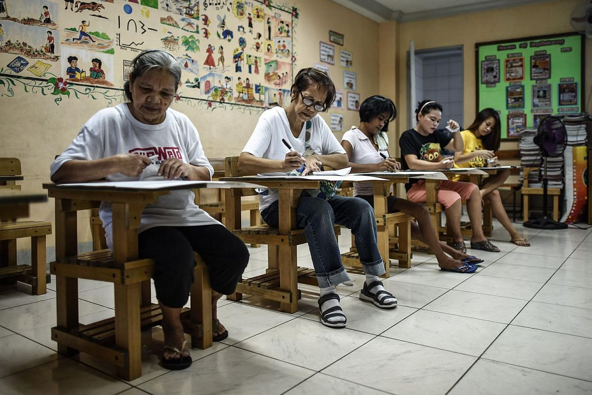 Filipino women cast their votes at a polling centre in Manila on May 9, 2016 during the presidential and vice presidential elections.