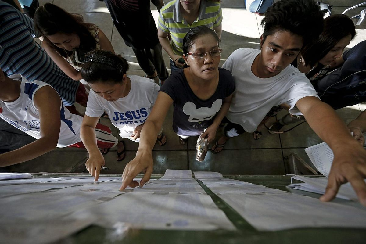 Filipinos looks for their names on the voters list inside a public school turned into a polling precinct in in Makati city, south of Manila, Philippines on May 9, 2016.