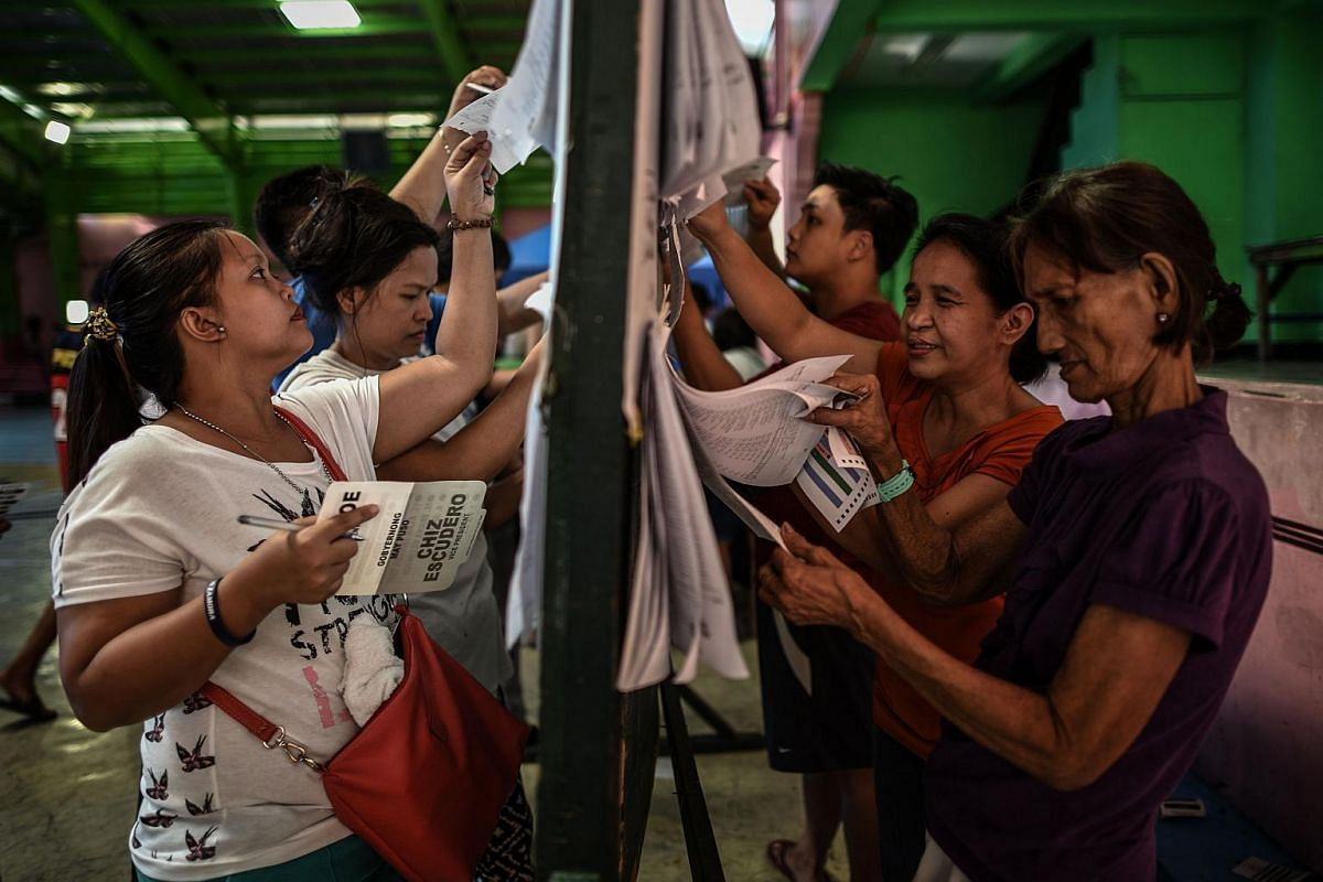 Filipino voters check for their names on lists before casting their votes in the country's presidential election at a polling centre in Manila on May 9, 2016.